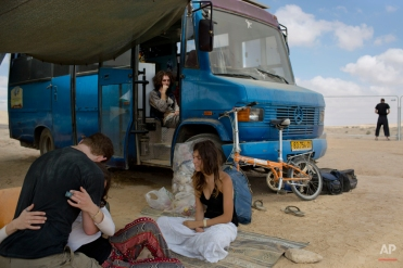 """In this photo taken Saturday, June 7, 2014, Israelis sits under the shade during Israel's first Midburn festival, modeled after the popular Burning Man festival held annually in the Black Rock Desert of Nevada, in the desert near the Israeli kibbutz of Sde Boker. For five days, participants, mostly Israelis ,created a temporary city dedicated to creativity, communal living, and what the festival calls """"radical self-expression."""" (AP Photo/Oded Balilty)"""