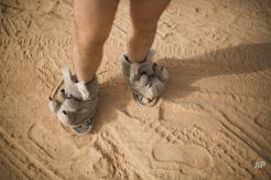 """In this photo taken Thursday, June 5, 2014, an Israeli man walks in house slippers during Israel's first Midburn festival, modeled after the popular Burning Man festival held annually in the Black Rock Desert of Nevada, in the desert near the Israeli kibbutz of Sde Boker. For five days, participants mostly Israelis created a temporary city dedicated to creativity, communal living, and what the festival calls """"radical self-expression."""" (AP Photo/Oded Balilty)"""