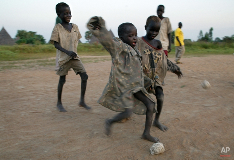 Children play with homemade soccer balls made from discarded medical gloves wrapped in bandages in the village of Nyal in southern Sudan, Nov. 20, 2003. (AP Photo/John Moore) License this image