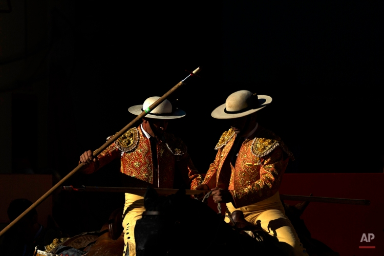 """A couple of picadors, horsemen with a spear that participates in a bullfight, wait before a bullfight of the San Fermin festival, in Pamplona, Spain, Monday, July 7, 2014. Revelers from around the world arrive in Pamplona every year to take part on some of the eight days of the running of the bulls glorified by Ernest Hemingway's 1926 novel """"The Sun Also Rises."""" (AP Photo/Daniel Ochoa de Olza)"""