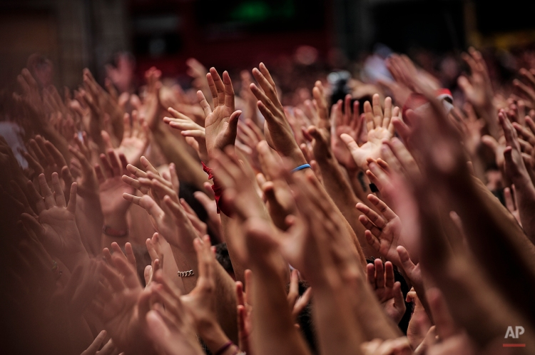 """Revelers hold up their hands during the launch of the 'Chupinazo' rocket, to celebrate the official opening of the 2014 San Fermin fiestas, in Pamplona, Spain, Sunday, July 6, 2014. Revelers from around the world kick off the festival with a messy party in the Pamplona town square, one day before the first of eight days of the running of the bulls glorified by Ernest Hemingway's 1926 novel """"The Sun Also Rises."""" (AP Photo/Alvaro Barrientos)"""