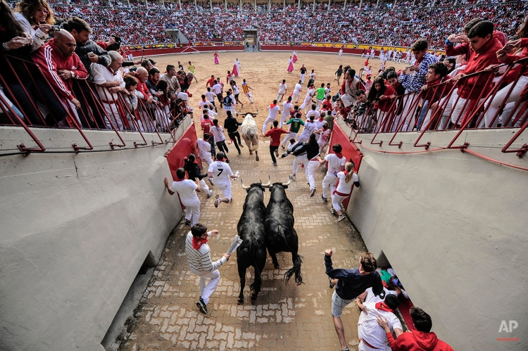 """Revelers arrive at the bull ring beside ''Dolores Aguirre Ybarra'' fighting bulls during the running of the bulls at the San Fermin festival, in Pamplona, Spain, Tuesday, July 8, 2014. Revelers from around the world arrive to Pamplona every year to take part in some of the eight days of the running of the bulls glorified by Ernest Hemingway's 1926 novel """"The Sun Also Rises."""" (AP Photo/Alvaro Barrientos)"""