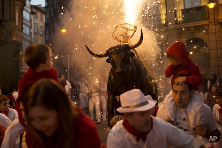 """Revelers run away followed by a flaming fake bull """"Toro de fuego"""" during the second day of the 2014 San Fermin fiestas in Pamplona, Spain, Monday, July 7, 2014. Revelers from around the world arrive to Pamplona every year to take part on some of the eight days of the running of the bulls glorified by Ernest Hemingway's 1926 novel """"The Sun Also Rises."""" (AP Photo/Andres Kudacki)"""