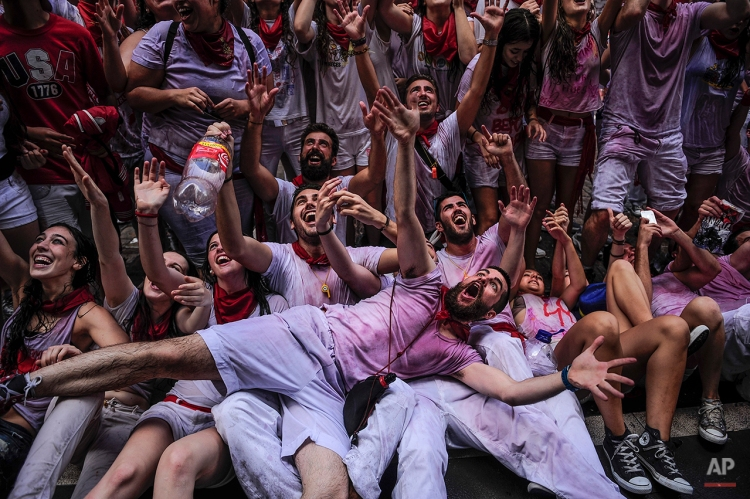 """Revelers celebrate during the launch of the 'Chupinazo' rocket, to celebrate the official opening of the 2014 San Fermin fiestas, in Pamplona, Spain, Sunday, July 6, 2014. Revelers from around the world kick off the festival with a messy party in the Pamplona town square, one day before the first of eight days of the running of the bulls glorified by Ernest Hemingway's 1926 novel """"The Sun Also Rises."""" (AP Photo/Alvaro Barrientos)"""