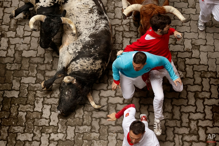 """Revelers run with Torrestrella ranch fighting bulls during the running of the bulls of the San Fermin festival, in Pamplona, Spain, Monday, July 7, 2014. Revelers from around the world arrive in Pamplona every year to take part on some of the eight days of the running of the bulls glorified by Ernest Hemingway's 1926 novel """"The Sun Also Rises."""" (AP Photo/Daniel Ochoa de Olza)"""