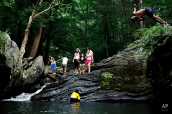 People cool off from the afternoon heat at the Devil's Pool in Wissahickon Valley Park, Friday, July 19, 2013, in Philadelphia. An excessive heat warning is again in effect for the Philadelphia region with highs expected to head up to the high-90s. (AP Photo/Matt Rourke)