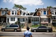 A police officer stands by two collapsed row houses Monday, July 7, 2014, in Philadelphia. Authorities say no injuries were reported in the collapses. (AP Photo/Matt Rourke)
