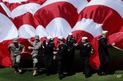 Members of the military unfurl a United States flag before Philadelphia Phillies' home opener baseball game against the Washington Nationals , Monday, April 12, 2010, in Philadelphia. (AP Photo/Matt Rourke)