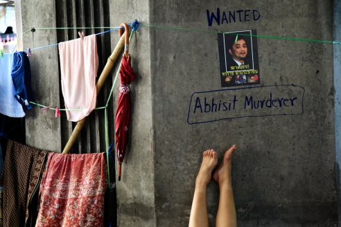 A woman sleeps under a defaced poster with a picture of Thailand's Prime Minister Abhisit Vejjajiva in the anti-government encampment on Monday May 10, 2010 in Bangkok, Thailand. Thailand's prime minister pleaded Sunday for an end to two months of street protests paralyzing part of the capital and an acceptance of his reconciliation plan that has been stalled by fresh violence. (AP Photo/Wong Maye-E) License this photo