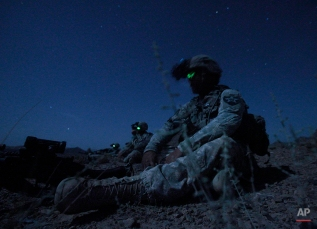 United States Army Spc. Kevin O'Connor, of Hingham, Mass., right, sits in the darkness with other members of United States Army Spc. Kevin O'Connor, of Hingham, Mass. during an ambush set up Friday, May 21, 2010 to catch Taliban fighters who had fired on their outpost earlier in the week, in Afghanistan's Kandahar province. (AP Photo/Julie Jacobson)