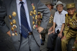 North Korean war veteran, Kim Hak Chol, 81, a retired soldier, right, together with other veterans decorated with medals, attend a parade to celebrate the anniversary of the Korean War armistice agreement, Sunday, July 27, 2014, in Pyongyang, North Korea. North Koreans gathered at Kim Il Sung Square as part of celebrations for the 61st anniversary of the armistice that ended the Korean War. (AP Photo/Wong Maye-E) License this photo
