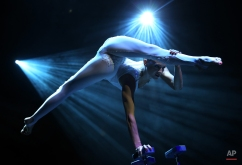 A member from the production Le Noir performs at the Marina Bay Sands on Tuesday March 12, 2013 in Singapore. Le Noir has a crew of twenty cirque performers from around the world like Russia, Australia, Lithuania, Canada, Bulgaria who specialize in different acrobatic acts, some of which were formerly from the production Cirque du Soleil. (AP Photo/Wong Maye-E) License this photo