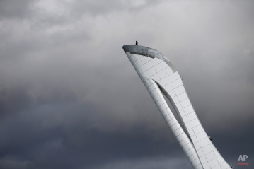 A worker is dwarfed against the sky as he stands at the top of the Olympic cauldron ahead of the 2014 Winter Olympics, Tuesday, Feb. 4, 2014, in Sochi, Russia. (AP Photo/Wong Maye-E) License this photo