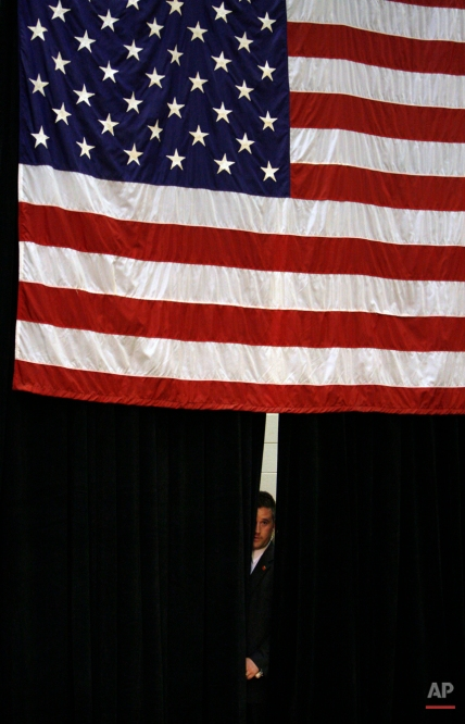 A Secret Service agent looks out from backstage before the arrival of Democratic presidential hopeful, Sen. Hillary Rodham Clinton, D-N.Y., at a campaign rally at Muncie Central High School in Muncie, Ind., Friday, March 28, 2008. (AP Photo/Charles Dharapak)