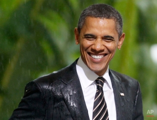 President Barack Obama smiles in the rain as he and French President Nicolas Sarkozy attend an event honoring the alliance between the United States and France and their efforts in Libya , Friday, Nov. 4, 2011, at Cannes City Hall, after the G20 Summit in Cannes, France. (AP Photo/Charles Dharapak)
