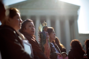 """Leonida Martinez, from Phoenix, Ariz., second from left, and others take part in a demonstration in front of the Supreme Court in Washington, Wednesday, April 25, 2012, as the court questions Arizona's """"show me your papers"""" immigration law. (AP Photo/Charles Dharapak)"""