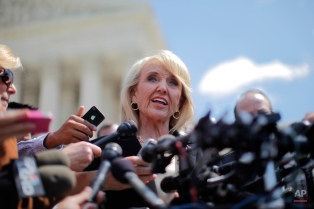 """Arizona Gov. Jan Brewer speaks to reporters outside the Supreme Court in Washington, Wednesday, April 25, 2012, after the court's hearing on Arizona's """"show me your papers"""" immigration law. (AP Photo/Charles Dharapak)"""