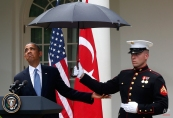 President Barack Obama looks to see if it is still raining as a Marine holds an umbrella for him during his joint news conference with Turkish Prime Minister Recep Tayyip Erdogan, not pictured, Thursday, May 16, 2013, in the Rose Garden of the White House in Washington. (AP Photo/Charles Dharapak)