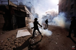 An Egyptian protestor throws away a tear gas canister fired by security forces during clashes near the Interior Ministry in Cairo, Egypt, Friday, Feb. 3, 2012. A volunteer doctor says police and protesters angry over a deadly soccer riot have clashed for the second day in the Egyptian capital, and that one man died in the latest violence. (AP Photo/Muhammed Muheisen)