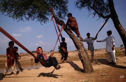 Pakistani Dawlat Gul, 7, third left, enjoys playing on a swing along with other children on the outskirts of Islamabad, Pakistan, Friday, July 13, 2012. (AP Photo/Muhammed Muheisen)