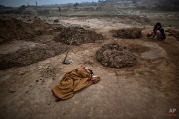 Pakistani boy, Adil Shahid, 6, suffering from a fever, sleeps on the ground wrapped with a shawl, next to his mother Najma, 25, at the site of her work in a brick factory in Mandra, near Rawalpindi, Pakistan, Monday, March 3, 2014. (AP Photo/Muhammed Muheisen)
