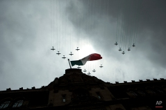 Mexican airforce aircraft, trailing the colors of the national flag fly over the National Palace during the finale of an annual Independence Day parade by Mexico's Armed Forces, in the Zocalo in central Mexico City, Tuesday, Sept. 16, 2014. (AP Photo/Rebecca Blackwell)