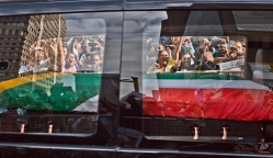 South African mourners, wave and shout as the hearse carrying the body of former South African President Nelson Mandela passes by, in Pretoria, South Africa, Thursday Dec. 12, 2013. (AP Photo/Muhammed Muheisen)