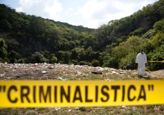 A forensic examiner walks along a garbage-strewn hillside above a ravine where examiners are searching for human remains in densely forested mountains outside Cocula, Guerrero state, Mexico, Tuesday, Oct. 28, 2014. (AP Photo/Rebecca Blackwell, Pool)