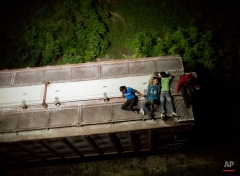 """In this Aug. 26, 2014 photo, Central American migrants rest atop the last boxcar of a moving freight train as it heads north from Arriaga toward Chahuites, Mexico. A Mexican crackdown seems to be keeping women and children off the deadly train, known as """"The Beast,"""" that has traditionally helped thousands of migrants head north. The once-open route to the United States has become so difficult that trains now carry a small fraction of the migrants they used to, and almost exclusively adult men. (AP Photo/Rebecca Blackwell)"""