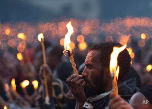 A man closes his eyes as he holds up his candle during a public candlelight memorial for late Prime Minister Meles Zenawi, at Meskel Square in Addis Ababa, Ethiopia Thursday, Aug. 30, 2012. Thousands turned out for the first of three days of planned commemorative ceremonies. (AP Photo/Rebecca Blackwell)