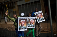 South African mourners hold posters of former president Nelson Mandela, while chanting slogans as the convoy transporting the body of Nelson Mandela passes by, in Pretoria, South Africa, Wednesday, Dec. 11, 2013. Motorcycle-riding police officers escorted the casket Wednesday morning from 1 Military Hospital outside of Pretoria to the Union Buildings. Some Pretoria residents lined the streets to watch the procession go by, singing tributes to Mandela, who died Dec. 5 at age 95. (AP Photo/Muhammed Muheisen)