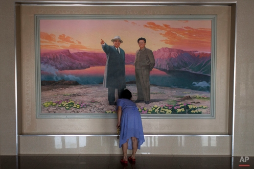 In this Friday, June 21, 2013 photo, a woman arranges flowers in front of a painting depicting the late leaders Kim Il Sung, left, and Kim Jong Il at the lobby of a hotel in Haeju city, South Hwanghae Province, North Korea. (AP Photo/Alexander F. Yuan)