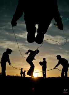 Palestinian youths and children play during sunset in the West Bank city of Ramallah, Saturday, Feb. 9, 2008. (AP Photo/Muhammed Muheisen)