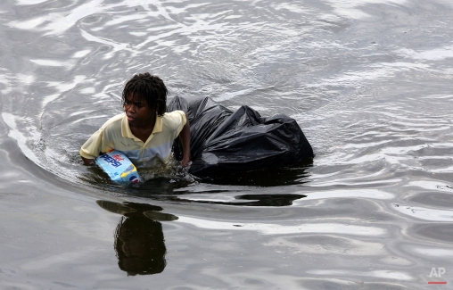 A young man walks through chest deep flood water after looting a grocery store in New Orleans on Tuesday, Aug. 30, 2005. (AP Photo/Dave Martin)