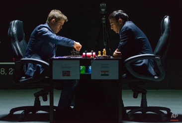 Norway's Magnus Carlsen, currently the top ranked chess player in the world, makes a move as he plays against India's former World Champion Vishwanathan Anand at the FIDE World Chess Championship Match in Sochi, Russia, Saturday, Nov. 8, 2014. (AP Photo/Artur Lebedev)