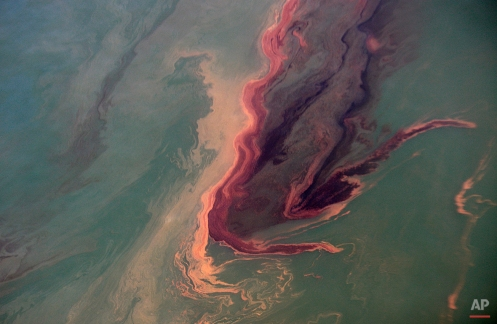 An oil slick near the site of the Deepwater Horizon oil spill contrasts with the water in the Gulf of Mexico Sunday, June 13, 2010. (AP Photo/Dave Martin)