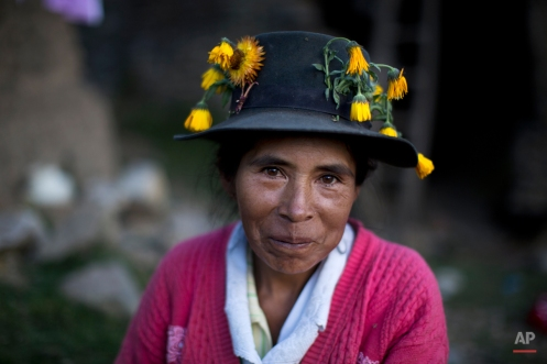 In this Oct. 29, 2014 photo, Gregoria Huaman poses for a portrait in her flower covered hat, common among women in the area, after burying her brother in law, Felix Huama, in Huallhua in Peru's Ayahuanco region. Felix Huaman and his brother-in-law Narcizo Cusiche were killed on June 14, 1990 while defending the town as members of the citizen self-defense force, so that villagers could escape from Shining Path militants, but their remains were only recently exhumed. Hundreds of such cases, most until now barely registered, are coming to light as forensic anthropologists methodically unearth victims of Peru's 1980-2000 dirty war absent government fanfare. (AP Photo/Rodrigo Abd)