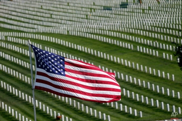 An American flag flies over war veterans tombstones at Golden Gate National Cemetery on Monday, Nov. 10, 2014, in San Bruno, Calif. The U.S. celebrates Veterans Day on Tuesday in honor of those who have served in the nation's military. (AP Photo/Marcio Jose Sanchez)