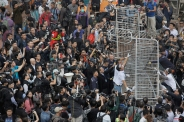 Workers start clearing away barricades at an occupied area outside government headquarters in Hong Kong Tuesday, Nov. 18, 2014. The removal comes after a Hong Kong court granted a restraining order against the protesters last week requiring them to clear the area in front of a tower in the central part of Hong Kong as well a separate order against a second protest site Mong Kok brought by taxi and minibus operators. (AP Photo/Vincent Yu)