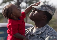National Guard soldier Carlos Clopton holds his son Caleb, 11-months, following a deployment ceremony at the Fort Deposit Municipal Complex in Fort Deposit, Ala., Wednesday, Feb. 15, 2012. (AP Photo/Dave Martin)