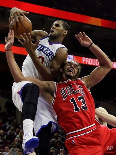 Philadelphia 76ers' Brandon Davies (0) battles for a rebound against Chicago Bulls' Joakim Noah (13) during the second half of an NBA basketball game, Friday, Nov. 7, 2014, in Philadelphia. Chicago won 118-115. (AP Photo/Matt Slocum)