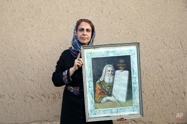 """In this Thursday, Nov. 20, 2014 photo, Iranian Jewish woman Rashel Hakkakian, holds a painting of Moses with """"The Ten Commandments,"""" after prayers at the Molla Agha Baba Synagogue, in the city of Yazd 420 miles (676 kilometers) south of capital Tehran. (AP Photo/Ebrahim Noroozi)"""