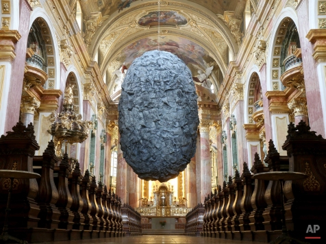 """A boulder plastic made of synthetic material called """"To be in Limbo hangs from the ceiling of the 20 meter high Jesuit Church in Vienna, Austria, Tuesday, Nov. 25, 2014. The eight meter high, hollow and 700 kilogram heavy sculpture from the artists group Steinbrener/Dempf and Huber is supposed to symbolize faith and its threatening moments. The installation will remain until April 19, 2015 and then move to a church in Hamburg, Germany. (AP Photo/Ronald Zak)"""