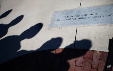 U.S. military service members cast a shadow next to a memorial as they stand during a Veterans Day ceremony at the Atlanta History Center, Tuesday, Nov. 11, 2014, in Atlanta. (AP Photo/David Goldman)