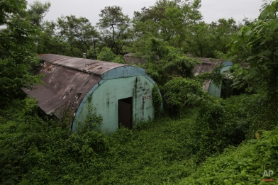 """In this Oct. 18, 2014, photo, a row of concrete structures called """"Quonset huts"""" lie inside the Subic Bay Freeport Zone, Zambales province, northern Philippines. The huts were used as barracks for U.S. Marines inside the former American naval base. It was closed in 1992 after the Philippine Senate voted not to extend the lease on the facility. Some of the abandoned huts were reused as dormitories and staff houses for employees. Other abandoned huts have not been touched since U.S. forces left 22 years ago. (AP Photo/Aaron Favila)"""