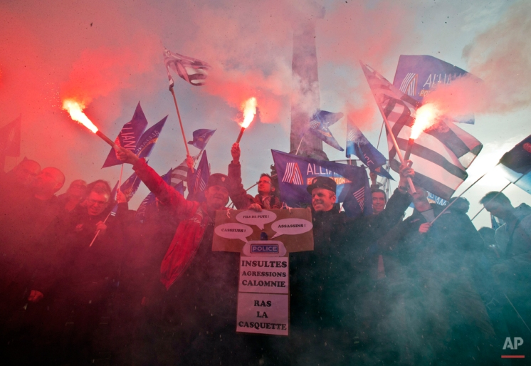 """Police officers holding flares as they march during a rally to demand better working conditions in Paris, Thursday, Nov. 13, 2014. Hundreds of students are barricading school entrances across Paris and demonstrating in protests against alleged police brutality, just as a major union of police officers staged its own rally to demand more personnel and equipment. Banner reads """"insults, agressions, calumny, fed up"""". (AP Photo/Michel Euler)"""