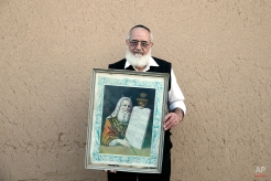 """In this Thursday, Nov. 20, 2014 photo, Iranian Jew Rahim Aqa Bala, 65, holds a painting of Moses with """"The Ten Commandments,"""" after prayers at the Molla Agha Baba Synagogue, in the city of Yazd 420 miles (676 kilometers) south of capital Tehran. (AP Photo/Ebrahim Noroozi)"""