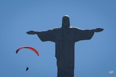 A paraglider flies around the Christ the Redeemer statue in Rio de Janeiro, Brazil, Monday, Nov. 17, 2014. (AP Photo/Felipe Dana)