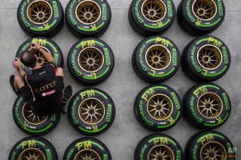 A Lotus crew member marks a tire in the boxes of the Interlagos circuit in Sao Paulo, Brazil, Thursday, Nov. 6, 2014. Formula One teams are in Sao Paulo to compete in the 2014 Brazilian Grand Prix, Sunday. (AP Photo/Felipe Dana)