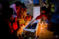 In this Oct. 28, 2014 photo, tears run down Udilia Ciguria Curo's face as she slowly inspect the remains of her brother Hector Curo Palomino during a one day candle lit wake inside the their home, as is local custom, in Huallhua, in Peru's Ayahuanco region. Curo was in his 20s when he was killed defending the town with two other members of the village's citizen self-defense force so villagers could escape from Shining Path militants on June 14, 1990. His remains were only recently exhumed and handed over to relatives, allowing them to bury him properly 24 years later. (AP Photo/Rodrigo Abd)